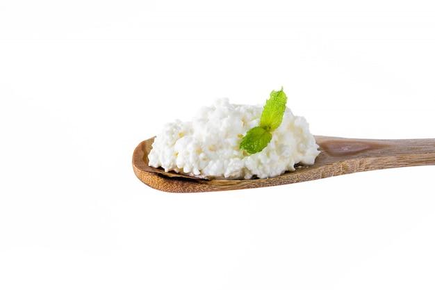 Ricotta fresca in un cucchiaio di legno isolato su bianco Foto Premium