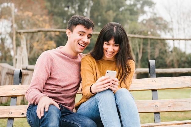 Ridere coppia seduta sulla panchina e guardando mobile Foto Gratuite
