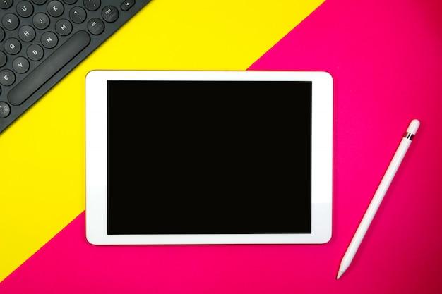 Riduca in pani la matita e la tastiera su tono del fondo due con lo spazio giallo e rosa della copia per testo Foto Premium