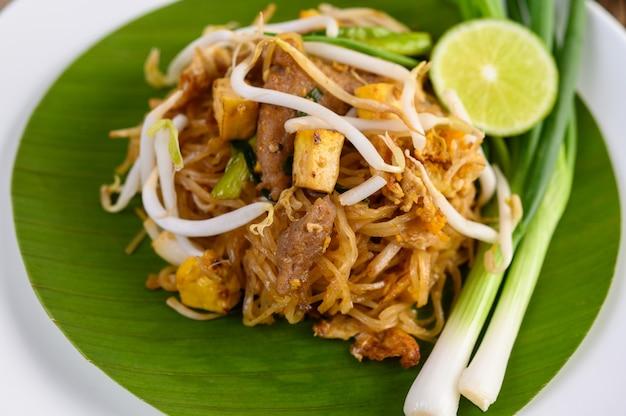 Riempia tailandese in un piatto bianco con il limone su una tavola di legno Foto Gratuite
