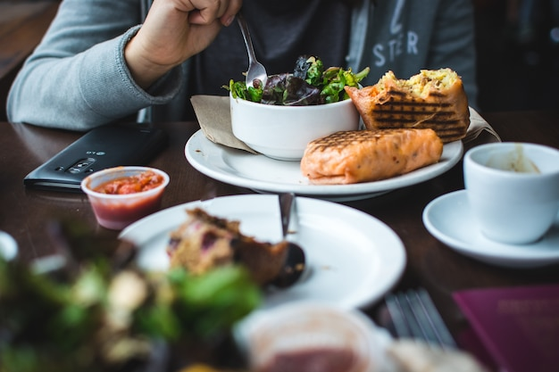 Riempire il burrito della prima colazione con insalata in un coffeeshop Foto Gratuite