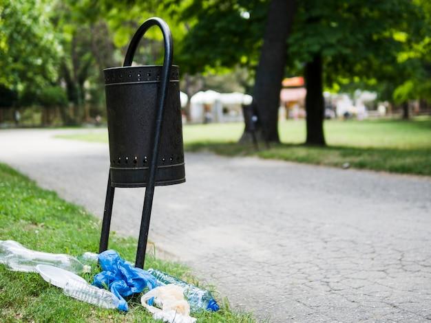 Rifiuti di plastica su erba vicino al bidone della spazzatura al parco Foto Gratuite