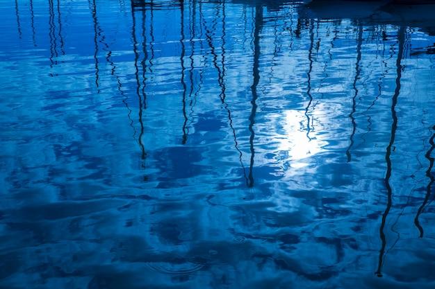 Riflessione dell'acqua blu dei pali delle barche delle barche a vela in onde Foto Premium
