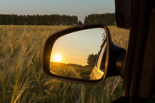 Riflessione nello specchio del tramonto nel campo di grano Foto Premium