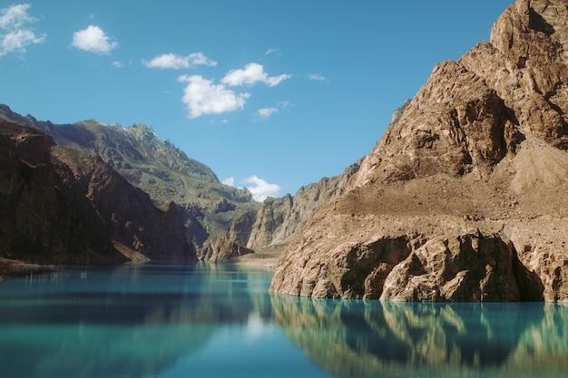 Riflesso nell'acqua del lago attabad, circondato da montagne nella catena del karakorum. Foto Premium