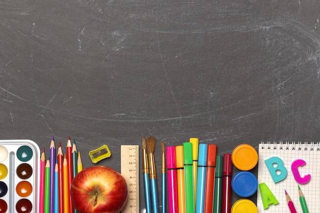 Rifornimenti di scuola sulla priorità bassa nera della lavagna. Foto Premium