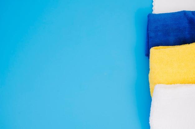 Riga del tovagliolo molle variopinto piegato contro priorità bassa blu Foto Gratuite