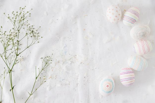 Riga delle uova di pasqua con i modelli vicino al ramoscello della pianta e piume sul tessuto Foto Gratuite