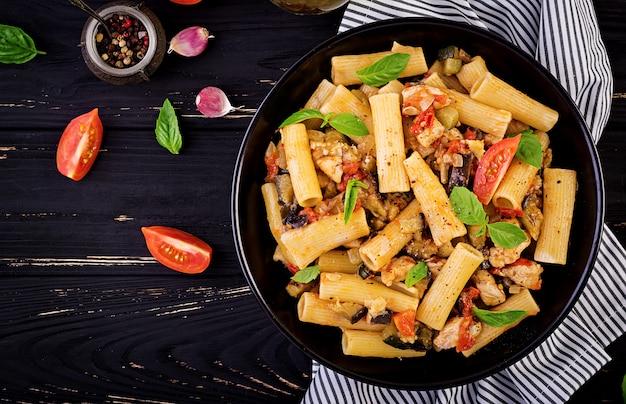 Rigatoni con carne di pollo, melanzane in salsa di pomodoro in ciotola. cucina italiana Foto Premium