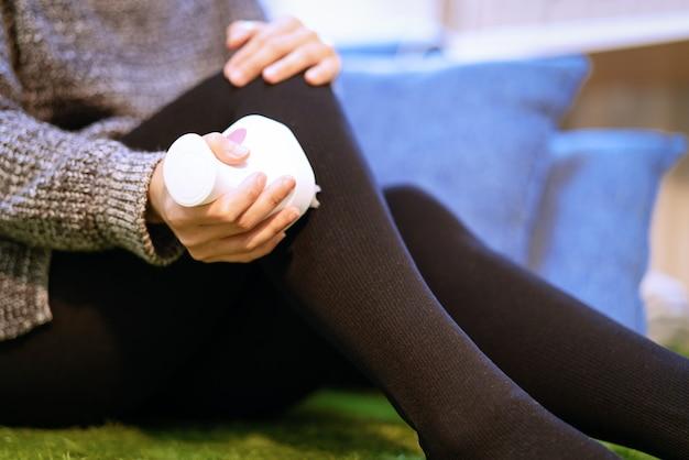 Rilassa e massaggia, macchina elettrica di massaggio del ginocchio e della gamba sulla gamba delle donne Foto Premium