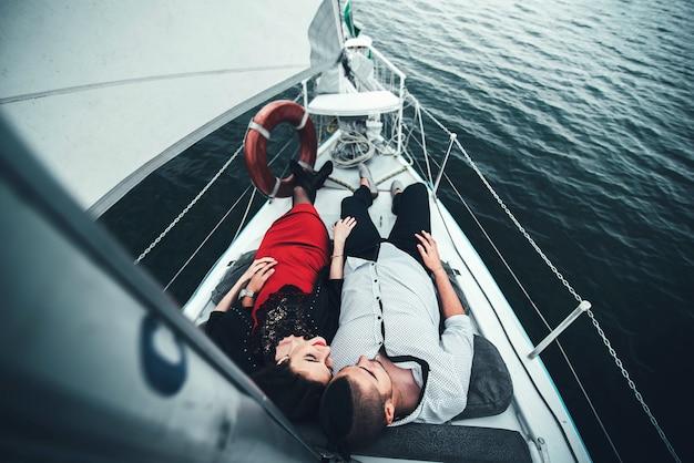 Rilassamento esterno delle coppie graziose sullo yacht Foto Premium