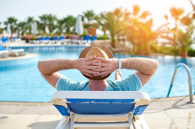 Rilassarsi in piscina estiva. giovane e riuscito uomo che si trova su una sdraio in hotel sullo sfondo del tramonto, tempo di concetto di viaggiare Foto Premium