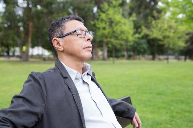 Rilassato uomo di mezza età seduto sulla panchina nel parco Foto Gratuite
