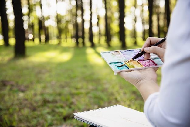 Rilassi l'opera d'arte dell'acquerello della pittura della donna in natura verde della foresta del giardino Foto Gratuite