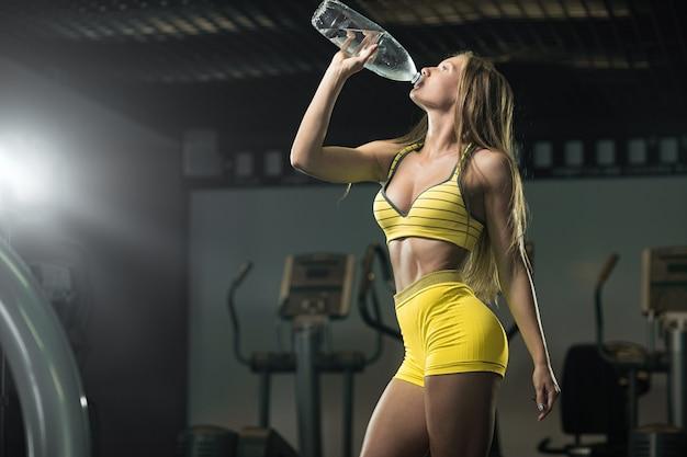 Rinfrescante dopo un allenamento. acqua potabile della bella donna in palestra Foto Premium