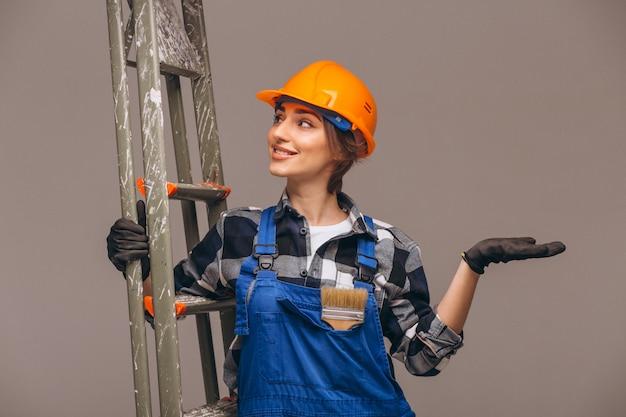 Riparatore della donna con la scala in un'uniforme isolata Foto Gratuite