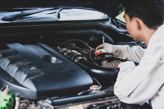 Riparatore di auto che indossa una divisa bianca in piedi e in possesso di una chiave che è uno strumento essenziale per un meccanico Foto Gratuite