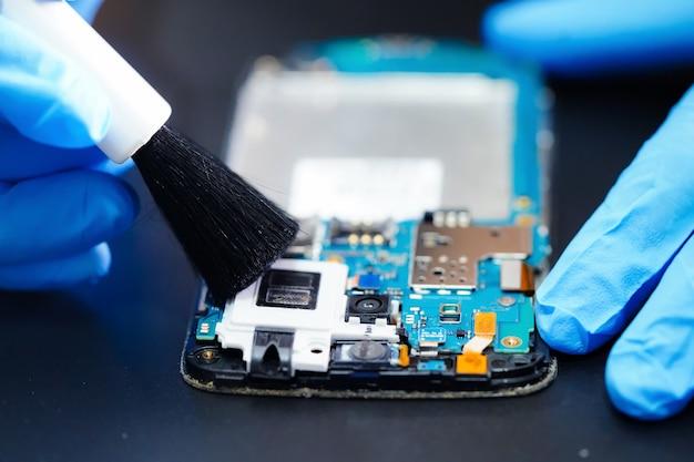 Riparazione asiatica del tecnico e pulizia del consiglio principale sporco del micro circuito dello smartphone. Foto Premium