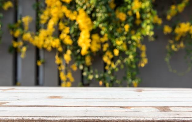 Ripiano del tavolo in legno d'epoca con bellissimi fiori gialli e foglie verdi Foto Premium
