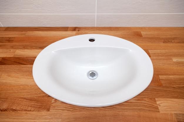 Ripiano del tavolo vuoto di legno del tek marrone del primo piano con il lavandino ceramico rotondo bianco. riparazione, rinnovo bagno in appartamenti, hotel, spa, impianto idraulico di installazione, rubinetto Foto Premium