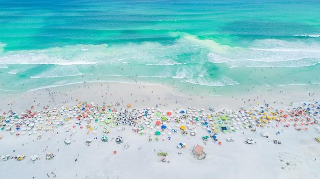 Ripresa aerea bloccata delle onde che si infrangono sulla riva. ombrelloni colorati e persone che si godono l'estate. Foto Premium