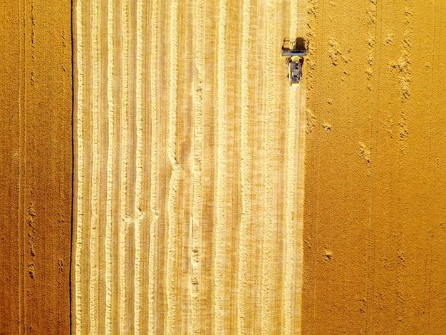 Ripresa aerea della mietitrice gialla che lavora al campo di frumento. Foto Premium