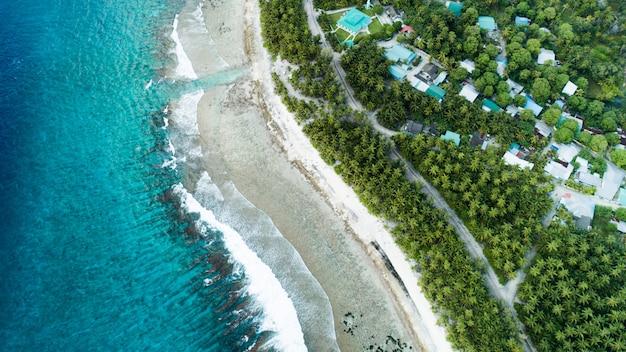 Ripresa aerea della spiaggia con le onde del mare e la giungla delle maldive Foto Gratuite