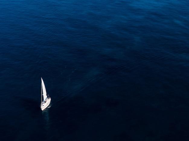 Ripresa aerea di una piccola barca bianca a vela nell'oceano Foto Gratuite