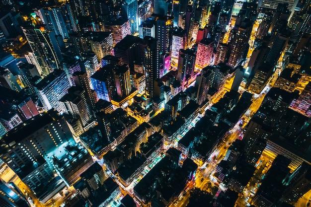 Ripresa aerea di uno scenario urbano con grattacieli che diffondono luce durante la notte Foto Gratuite