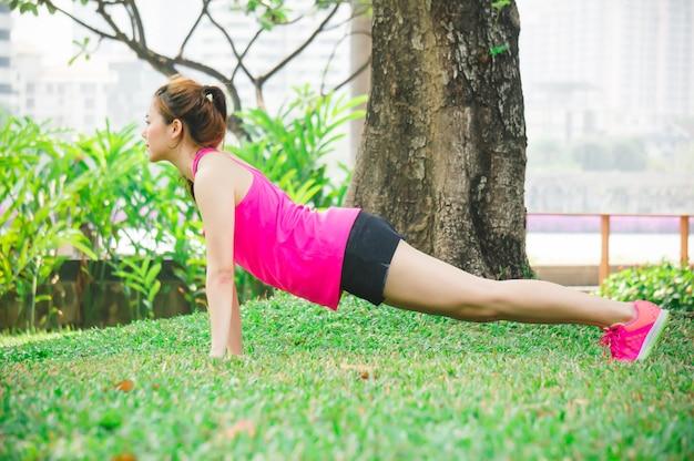 Riscaldamento asiatico della donna per esercitarsi dal piegamento sulle spalle del peso corporeo sui prati inglesi verdi in parco Foto Premium