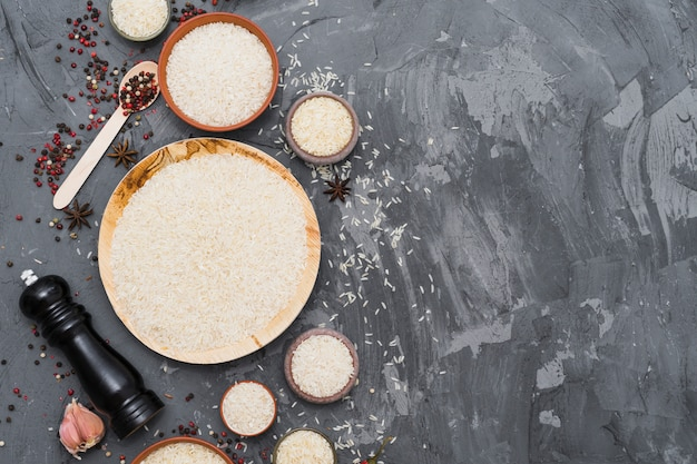 Riso bianco crudo con spezie secche; spicchio d'aglio e macinapepe su fondale in cemento Foto Gratuite