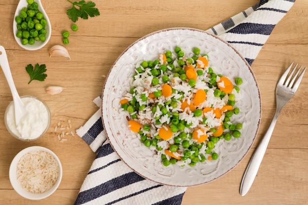 Riso con i fagiolini e la carota sul piatto vicino a salsa in ciotola sul tavolo Foto Gratuite