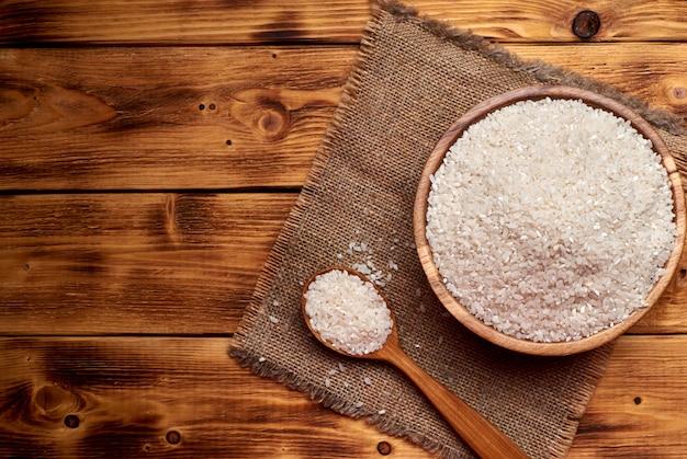 Riso crudo in una ciotola di legno con il cucchiaio di legno pieno di riso, fondo rustico. Foto Premium