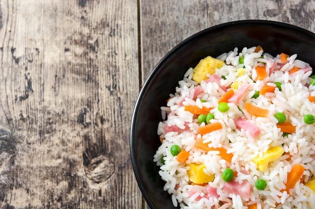 Riso fritto cinese con le verdure e l'omelette in ciotola nera sulla tavola di legno Foto Premium