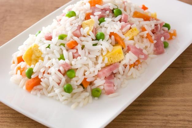 Riso fritto cinese con le verdure e l'omelette sulla fine di legno della tavola su Foto Premium