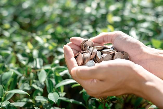 Risparmia il concetto dei soldi con le monete della tenuta della mano Foto Premium