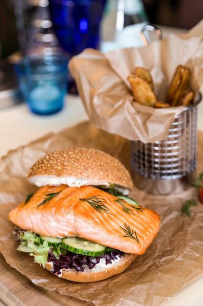 Ristorante che serve piatto - hamburger con salmone, patate fritte su tavola di legno Foto Premium