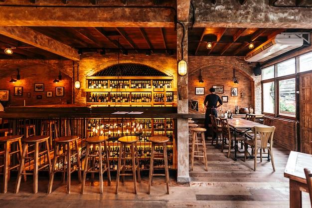 Ristorante italiano decorato con mattoni in una luce calda che ha creato un'atmosfera accogliente con il cameriere sul tavolo giusto. contro tavolo con cantina sul muro. Foto Premium
