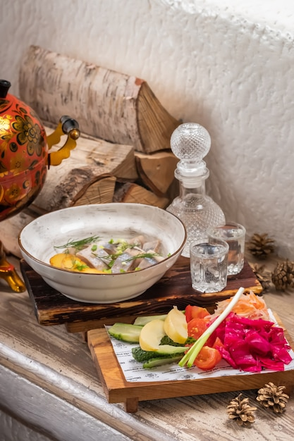 Ristorante menu di pesce con aringhe salate con anelli di cipolla e patate a cubetti bollite su un elegante piatto da ristorante con set di vodka fredda alcolica e salamoia assortita. Foto Premium