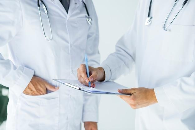 Ritaglia i dottori scrivendo una prescrizione Foto Gratuite