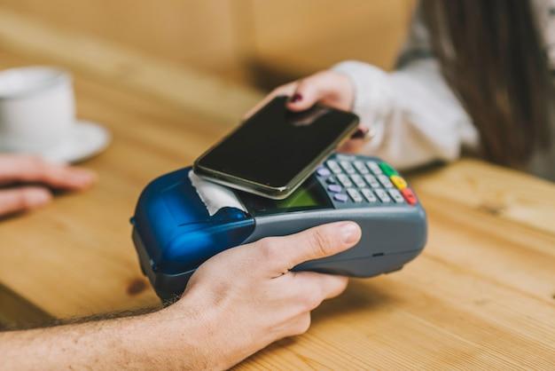 Ritaglia il cliente pagando con lo smartphone nella caffetteria Foto Gratuite