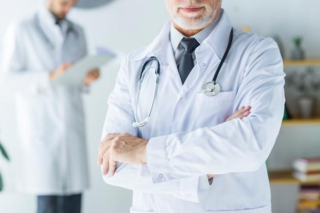 Ritaglia il medico fiducioso in ufficio Foto Gratuite