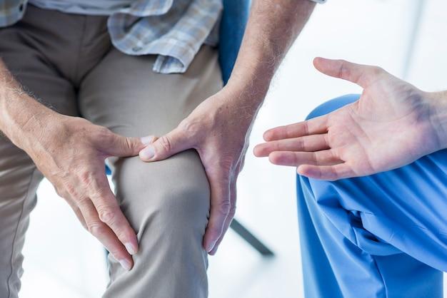 Ritaglia il paziente mostrando il ginocchio dolorante al dottore Foto Gratuite