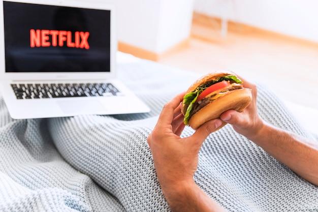 Ritaglia il ragazzo mangiando e guardando i programmi di netflix Foto Gratuite