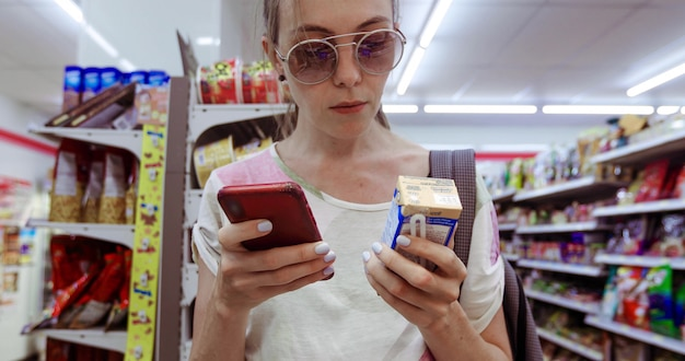 Ritaglia la giovane femmina in occhiali da sole che stanno nella drogheria e che utilizzano la casella di controllo del telefono della bevanda fresca Foto Premium