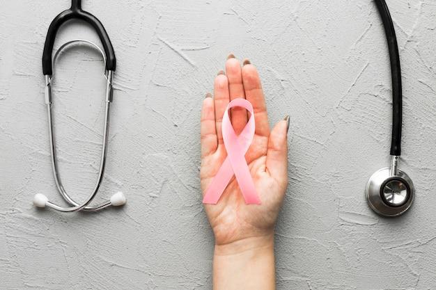 Ritaglia la mano con nastro rosa vicino stetoscopio Foto Gratuite