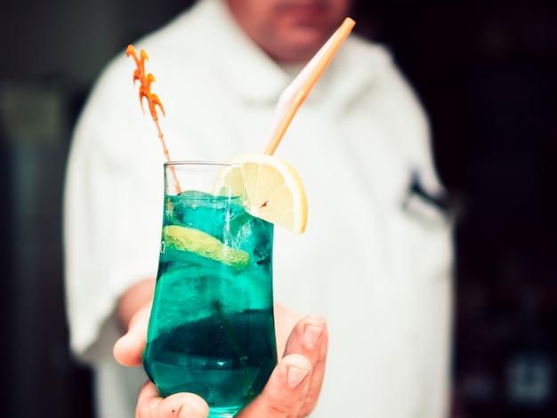 Ritaglia la mano del barista anonimo passando una bevanda rinfrescante Foto Gratuite