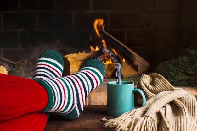 Ritaglia le gambe e le bevande vicino al camino e alla sciarpa Foto Gratuite