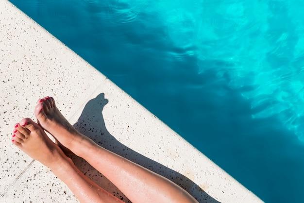 Ritaglia le gambe femminili a bordo piscina Foto Gratuite