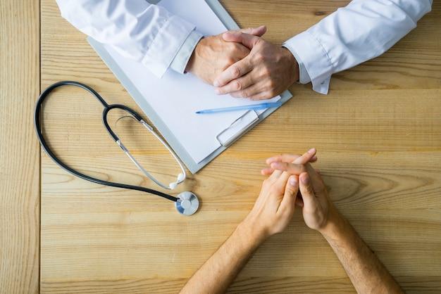 Ritaglia le mani del paziente maschio e del medico sul tavolo Foto Gratuite